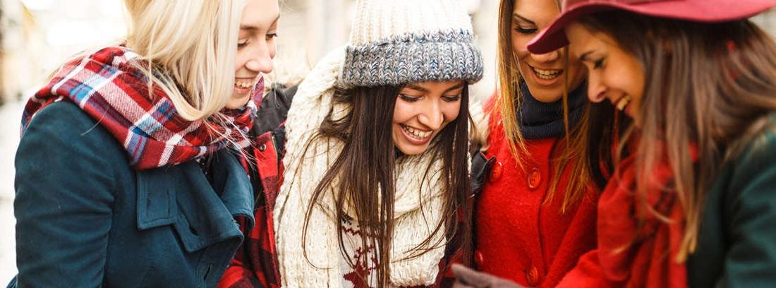 Mujer con gorro rojo y borde mira teléfono móvil con gesto alegre