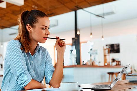 Mujer joven delante de un ordenador portátil y con un lápiz en la mano