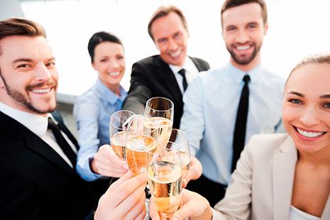 Hombres y mujeres sonrientes juntando copas llenas delante de ellos