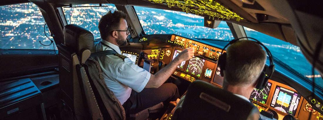 Dos personas de espaldas delante de un cuadro de mandos de un avión