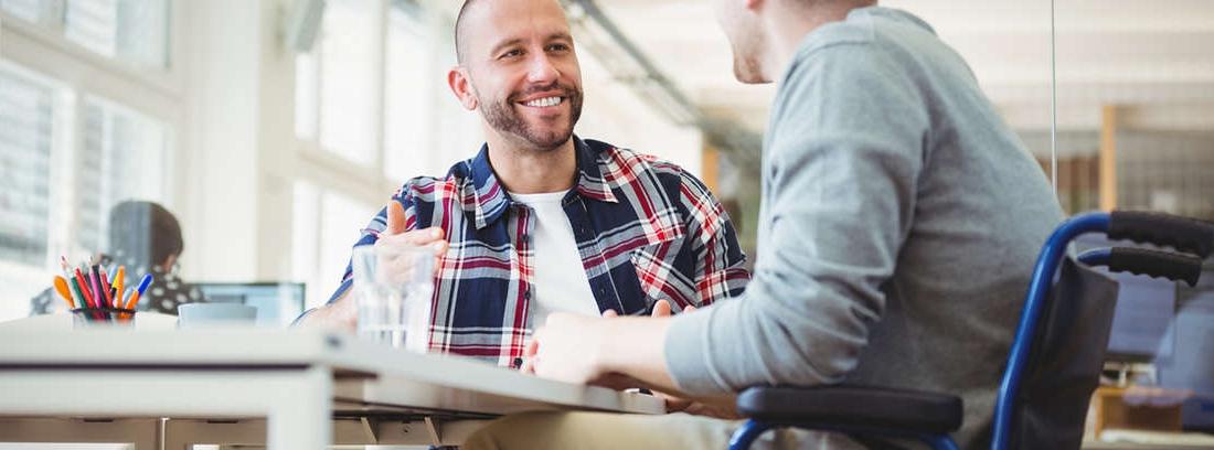 Un hombre en silla de ruedas mira un teléfono móvil en una mesa de trabajo junto a otro hombre sonriente.