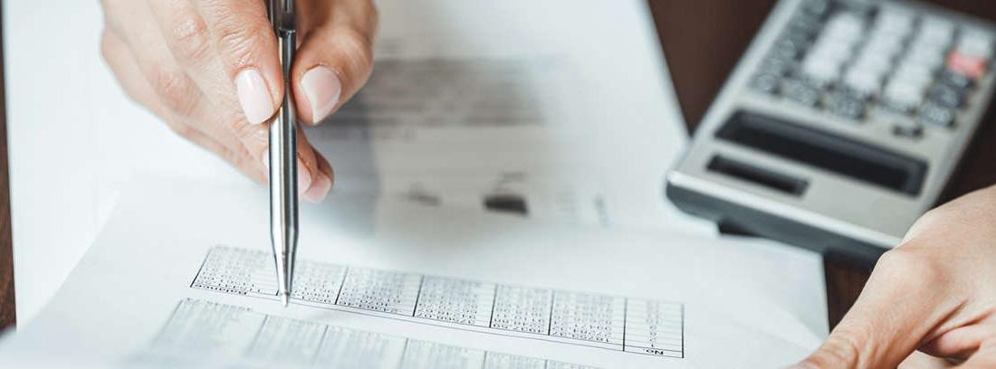 Hombre rodeados de papeles volando y cabeza entre las manos sobre archivadores