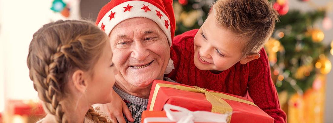 Hombre y mujer con pelo blanco miran sonrientes y sorprendido una caja abierta