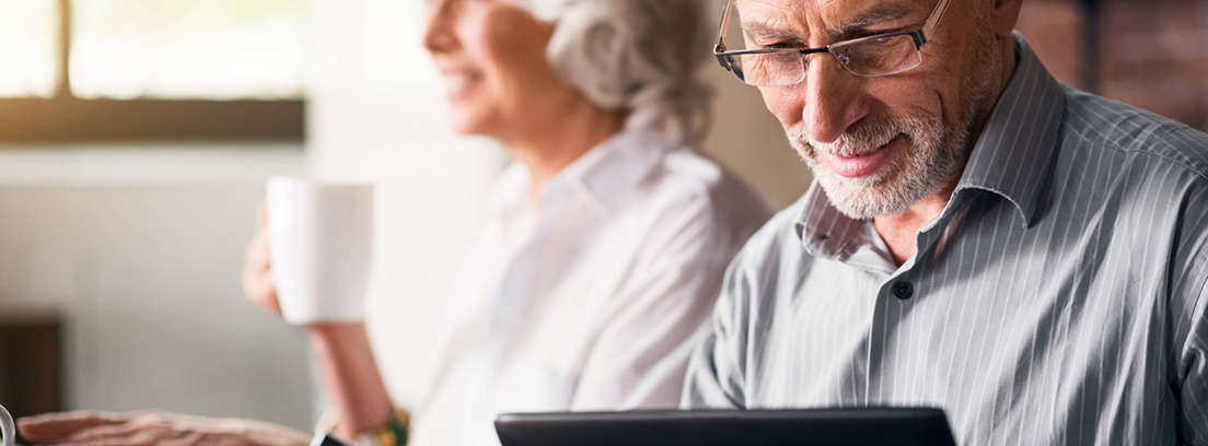 Hombre y mujer maduros sonrientes delante de la pantalla de ordenador portátil
