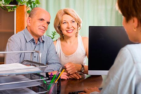 Hombre y mujer sentados a una mesa frente a ellos ordenador y otra persona