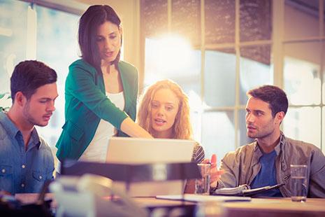 Mujer de pie señala en una pantalla hacia el que miran hombres y mujeres sentados