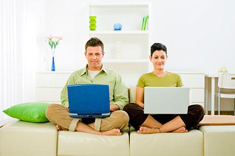 Hombre y mujer sentados en un sillón y con ordenadores portátiles sobre sus rodillas