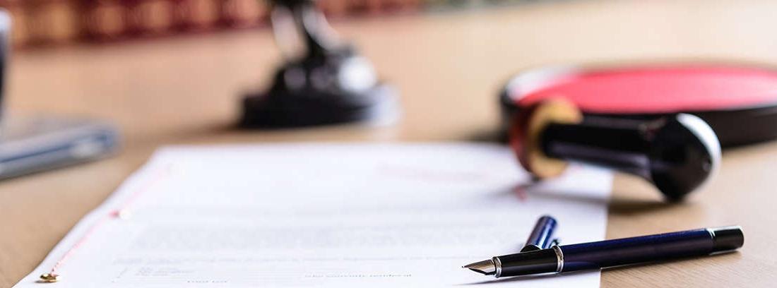 Pluma estilográfica sobre papel y junto a rollo lacrado y sello