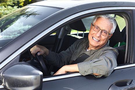 Hombre con pelo cano y gafas al volante de un coche