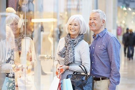 Hombre y mujer con pelo blanco sonrientes mirando un escaparate
