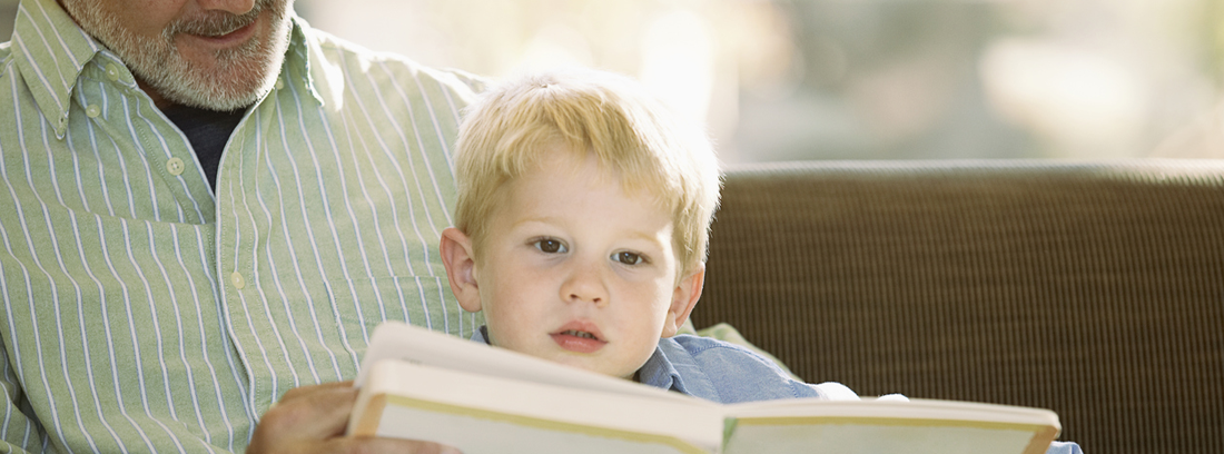 Hombre con pelo blanco tumbado en hierba junto a niño y mirando libro