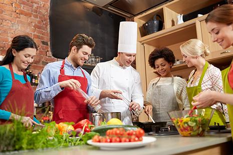 Hombre con uniforme de cocinero y junto a otras personas con delantal