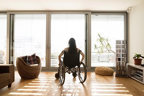 Mujer de espaldas en silla de ruedas mirando por un amplio ventanal