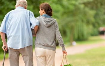 Hombre joven sonriente mira y sujeta por los hombros a mujer con bastón y pelo blanco