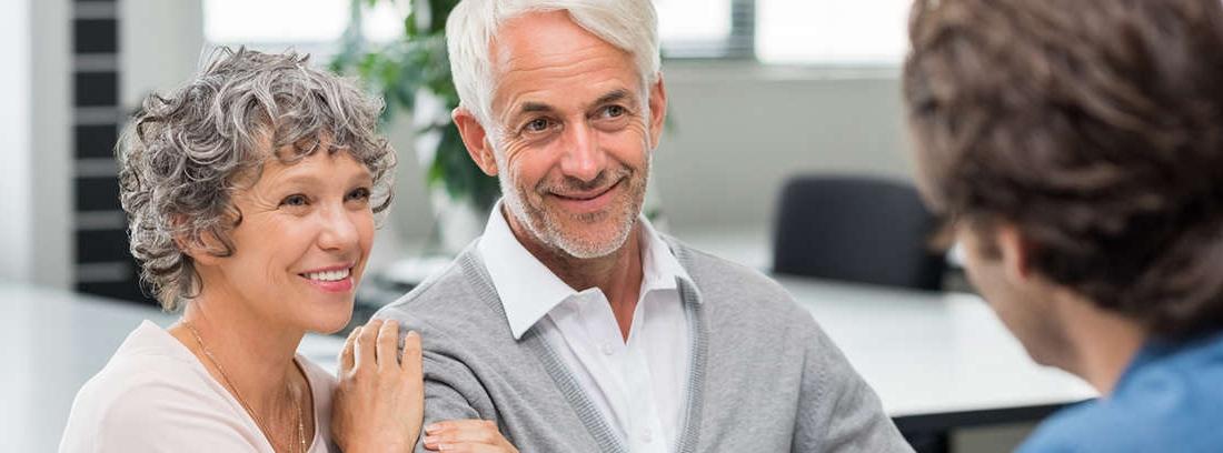 Hombre con pelo blanco y mujer sonriente con bolígrafos sobre papeles en una mesa