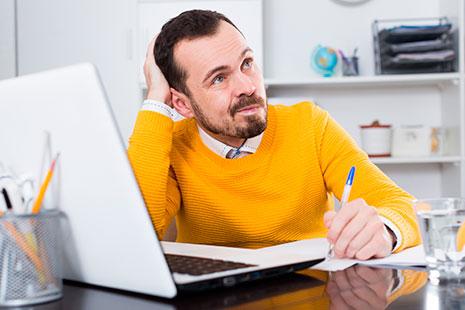 Hombre con ceño fruncido se toca la cabeza frente a ordenador portátil