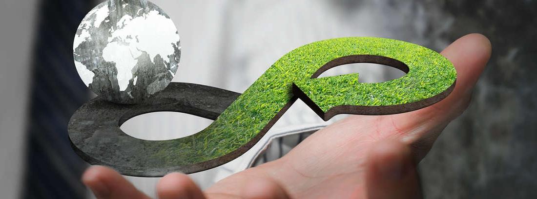 Mano sostiene un infinito verde con dos bolas del mundo en sus extremos
