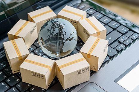 Gráfico de una bola del mundo rodeada de cajas de cartón sobre el teclado de un ordenador