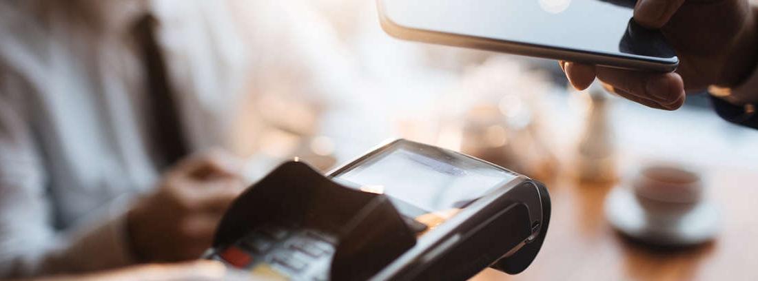 Persona pagando con teléfono móvil