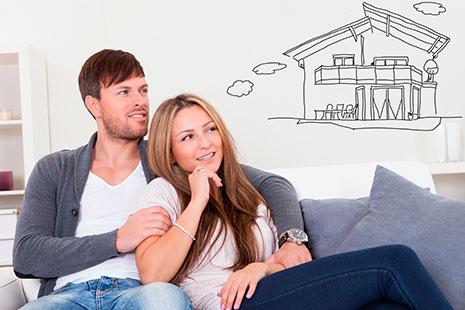 Hombre y mujer sentados en sofá y sobre ellos el dibujo de una casa