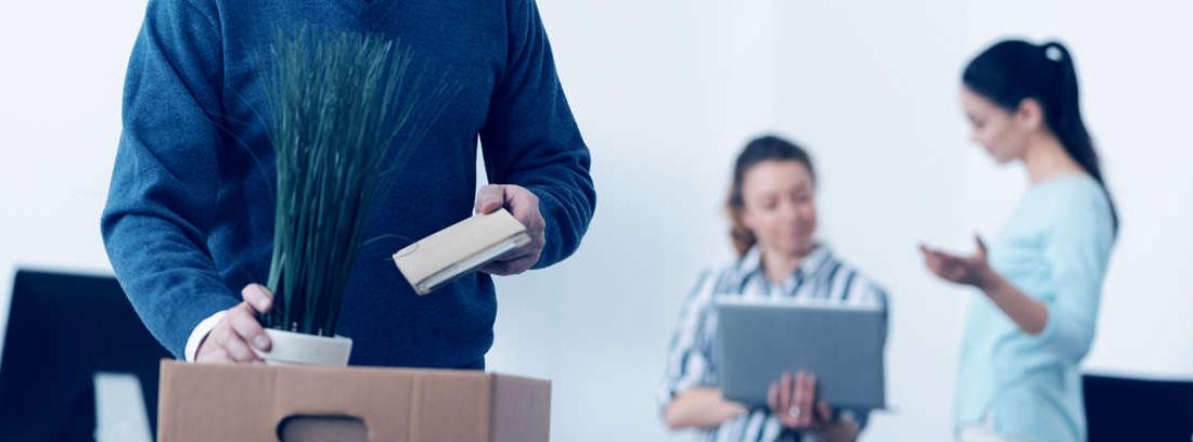 Hombre con pelo blanco con caja de cartón en una mano y teléfono móvil en la otra
