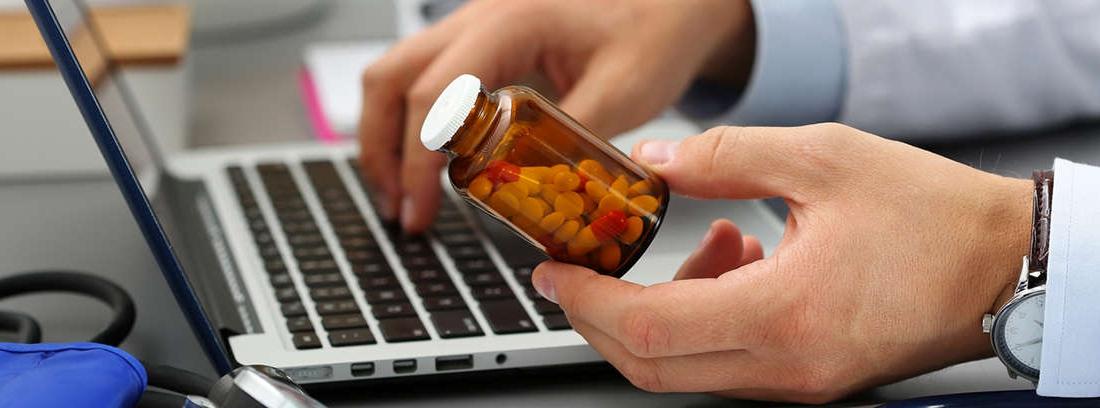 Manos usando un ordenador y sujetando un frasco con pastillas