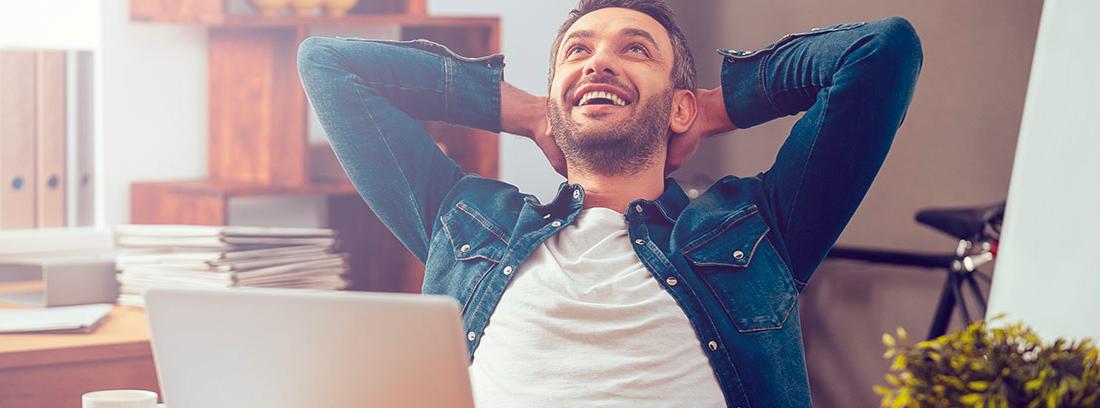 Hombre con las manos en la nuca y gesto alegre frente a una mesa con un ordenador