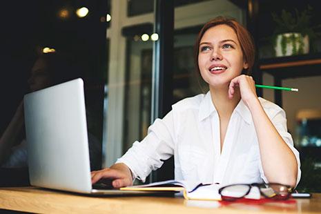 Mujer sonriente delante de ordenador portátil con lápiz en la mano