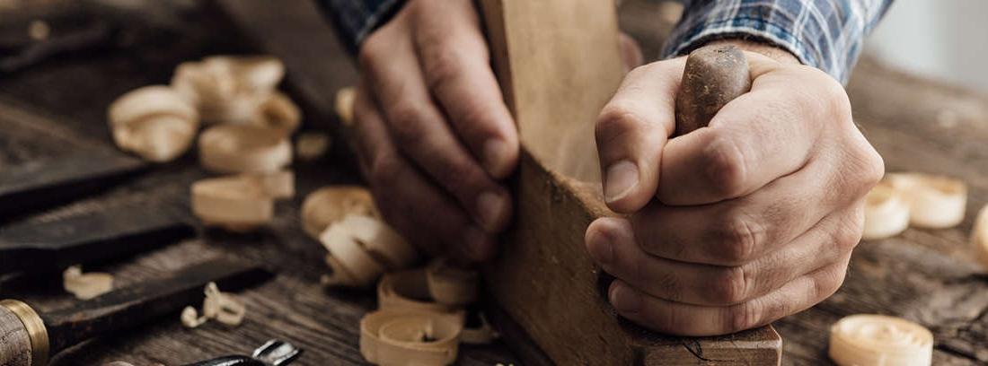 Manos con herramienta trabajando sobre una cadena metálica apoyada sobre madera