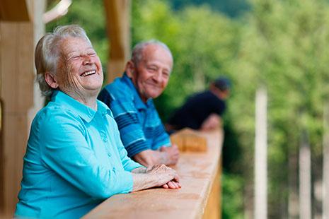 Una pareja de jubilados con camiseta azul, sonriendo en un bosque