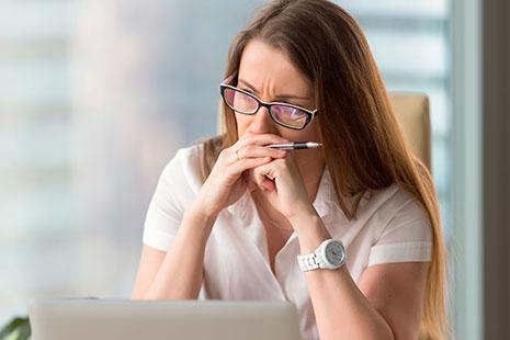 Mujer con gafas y manos sosteniendo bolígrafo sobre la boca mira hacia ordenador