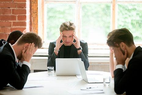 Tres hombres con manos en sus sienes y sentados a una misma mesa
