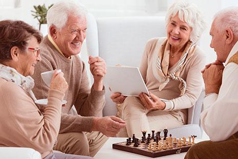 Personas mayores alrededor de un tablero de ajedrez