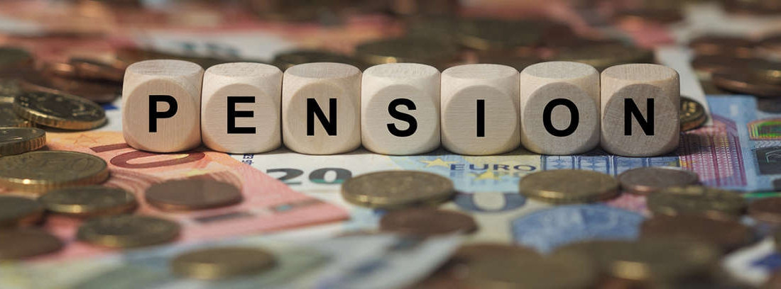 Palabra pensión impresa en etiqueta blanca al lado de calculadora, bolígrafo y monedas