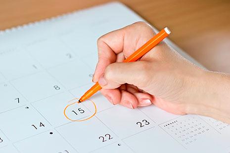 Mano femenina marcando un número del calendario de impuestos