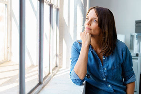 Mujer mirando a través de una ventana con el mentón apoyado en su puño