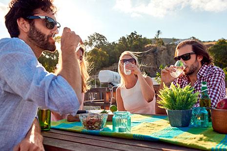 Dos hombres y dos mujeres sentados alrededor de una mesa al aire libre bebiendo de unos vasos.