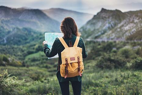 Mujer de espaldas con mochila amarilla y consultando mapa frente a montañas