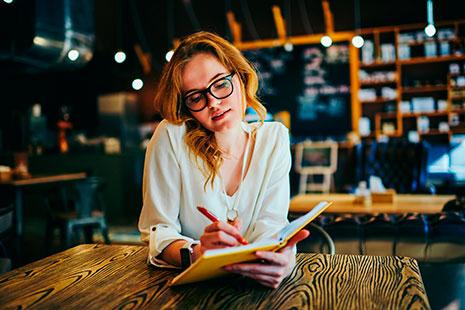 Mujer con gafas apunta con bolígrafo sobre un cuaderno
