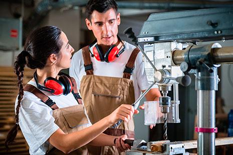 Hombre y mujer con peto de trabajo y protectores de oído manipulan máquina