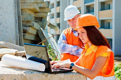 Mujer con casco naranja y chaleco frente a ordenador y junto a hombre con casco blanco