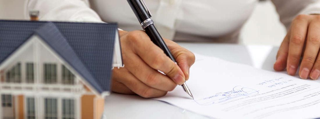 Hombre con mano sobre la boca y mujer miran a una mesa con papeles y calculadora