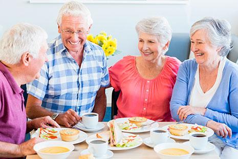 Hombre y mujeres de pelo blanco sentados a una mesa con comida y sonrientes