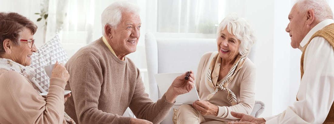 Hombre y mujer de pelo canoso sentados miran pantalla ordenador portátil