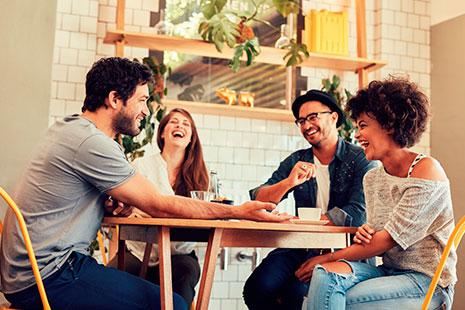 Hombre y mujeres sentados alrededor de una mesa riendo