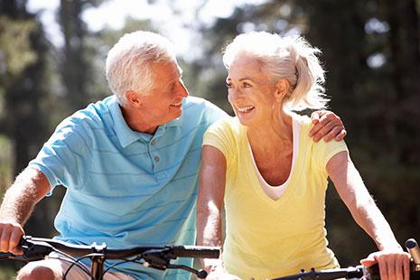 Hombre con pelo blanco sobre bici sujeta por el hombro a mujer en bici