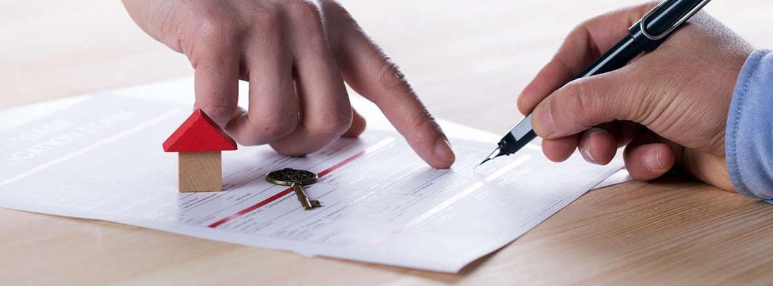 Manos sujetan papel escrito que firma otra mano junto a maqueta de casa y llaves