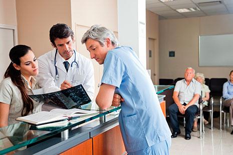 Hombre con uniforme sanitario azul, otro con bata blanca y mujer miran radiografía