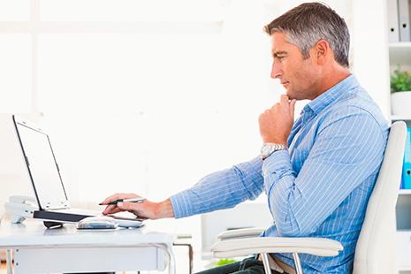Hombre de pelo cano con mano sobre barbilla delante de ordenador