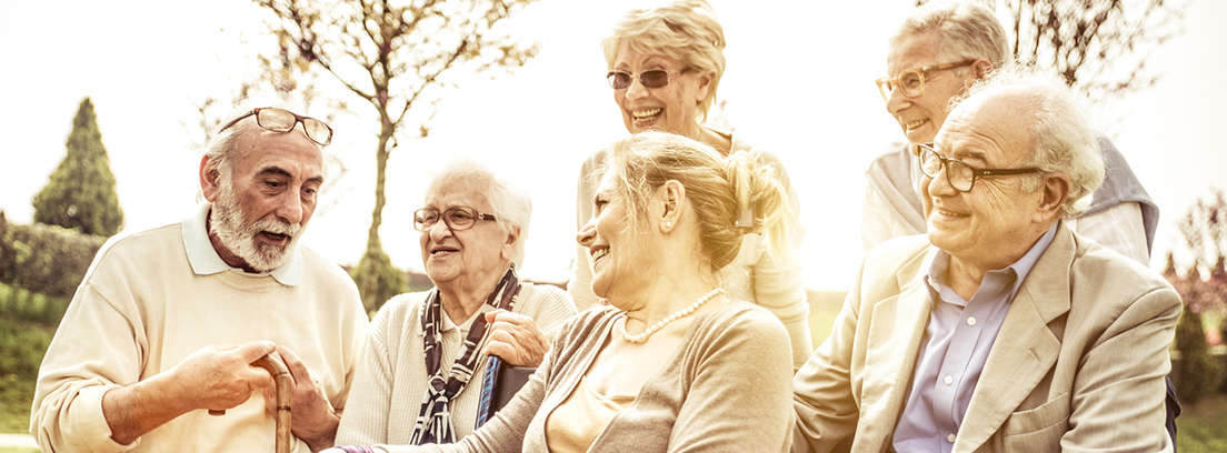 Hombre con pelo blanco y mujer con copa en la mano se miran sonrientes